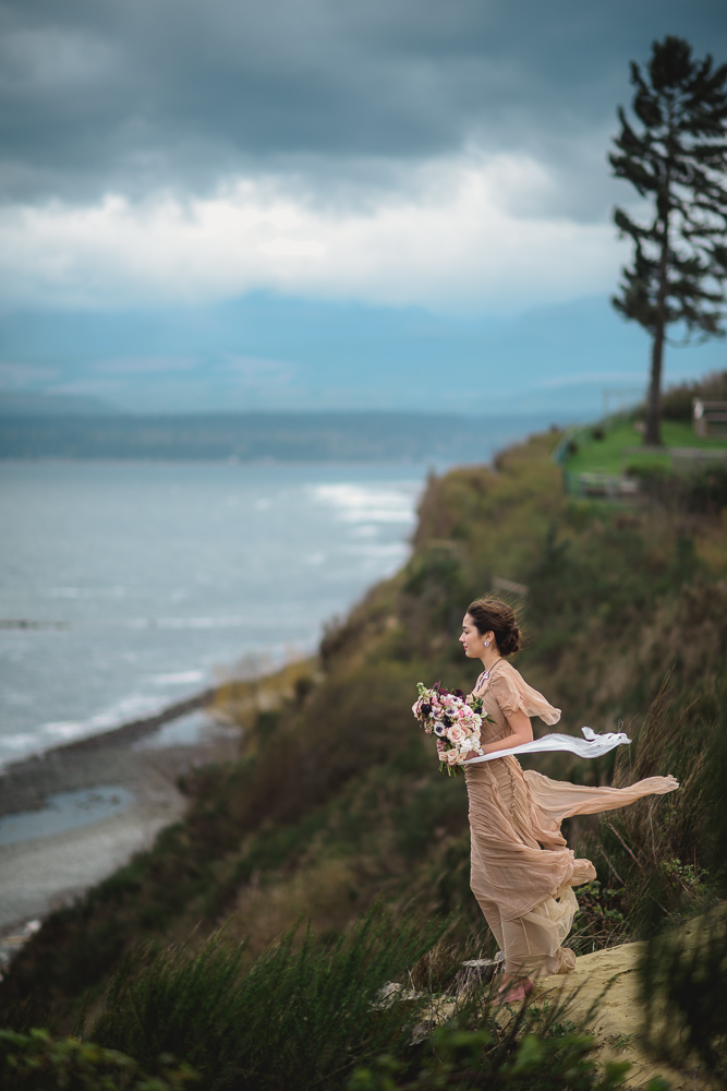 Bride on Cliff in Wind Colours of the Wind Erin Wallis Photography West Coast Weddings Magazine