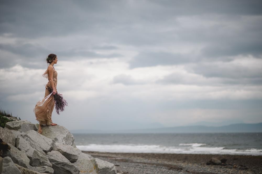 Bride on Rocks looking at oceanColours of the Wind Erin Wallis Photography West Coast Weddings Magazine