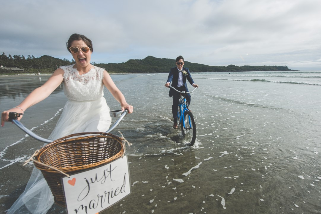 Wedding Couple Riding Bicycles on Beach West Coast Elope Vancouver Island Wedding Magazine
