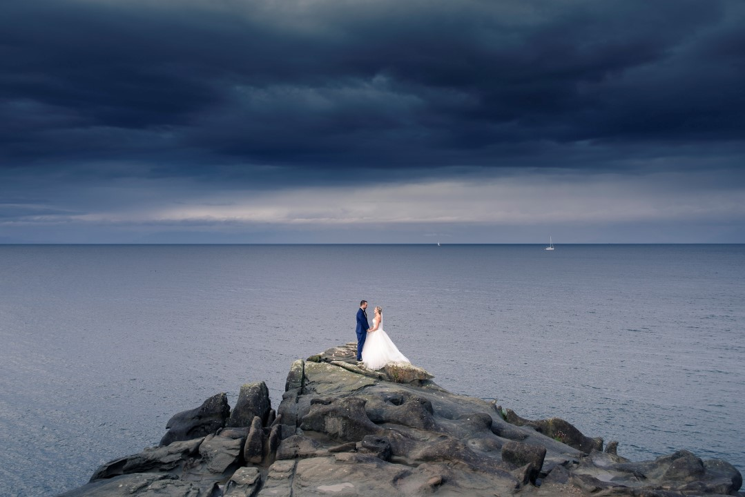 Newlyweds on Cliff Ocean View West Coast Weddings Magazine