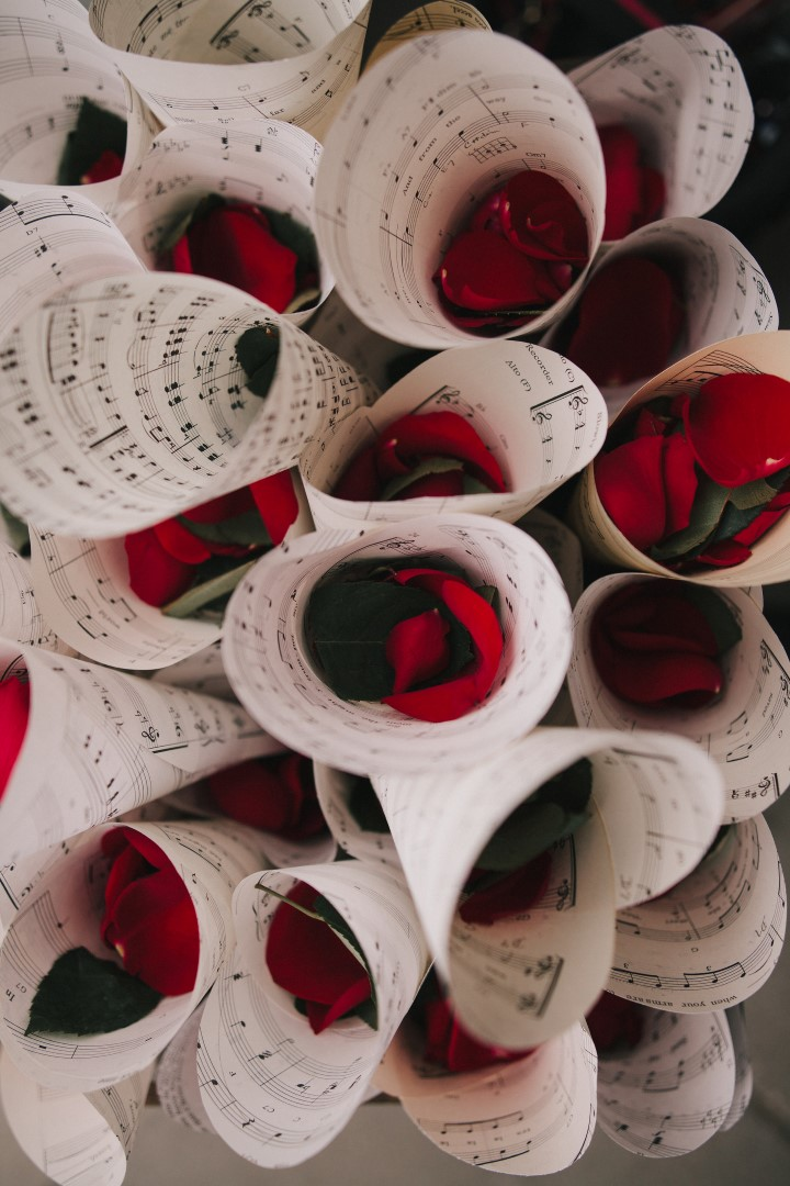 Red Rose Petals Wrapped in Vintage Music Sheets Gothic Dark Elegance West Coast Weddings Magazine