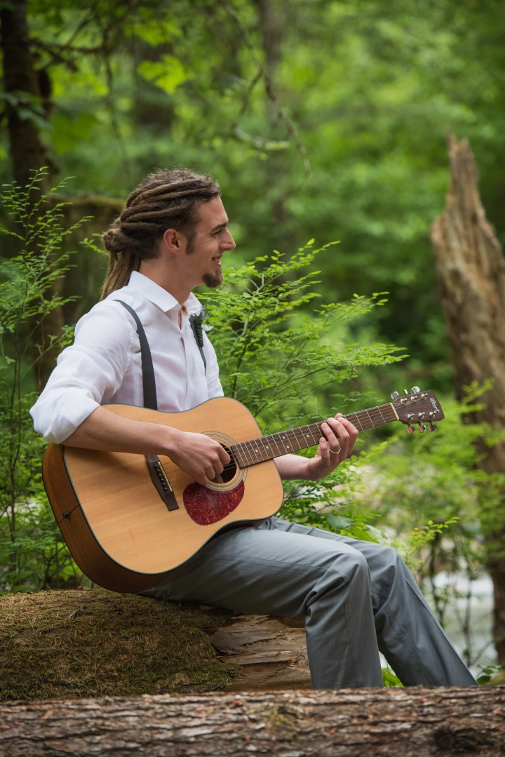 Groom playing Guitar in forest River Romance Vancouver Island wedding