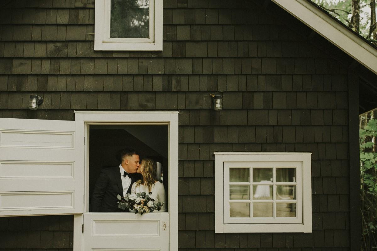 Newlyweds Kiss in Barn Door Elegant Woodland West Coast Weddings Magazine Vancovuer