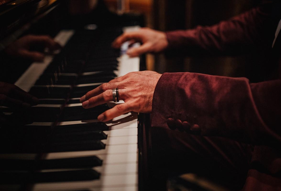 A Glamorous Holiday Wedding Groom Plays Piano with Wedding Band