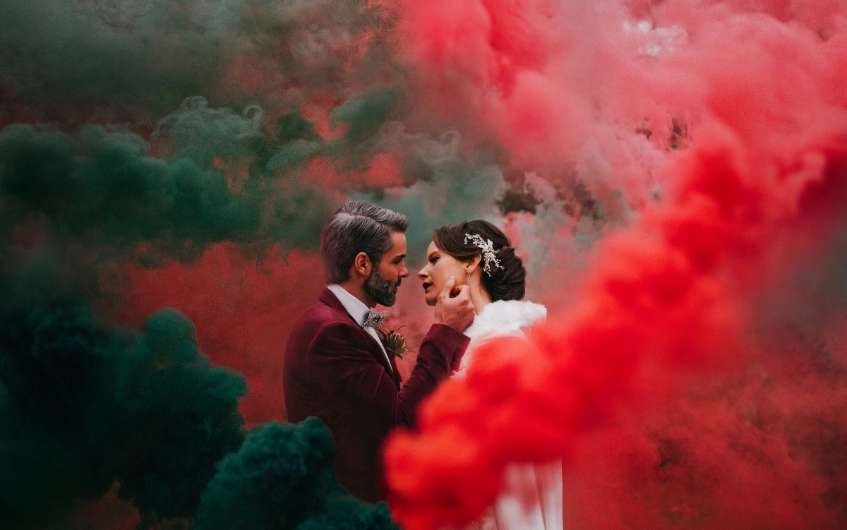 Newlyweds in red smoke bomb Holiday Glamour at Oak Bay Beach Hotel   Tasha Cline Photography   Beauty Bride   Cake by Taryn   Jennigs the Florist   Bliss Gowns & Events   Madison Paige Hair   Pretty Please Makeup Artistry   West Coast Weddings Magazine