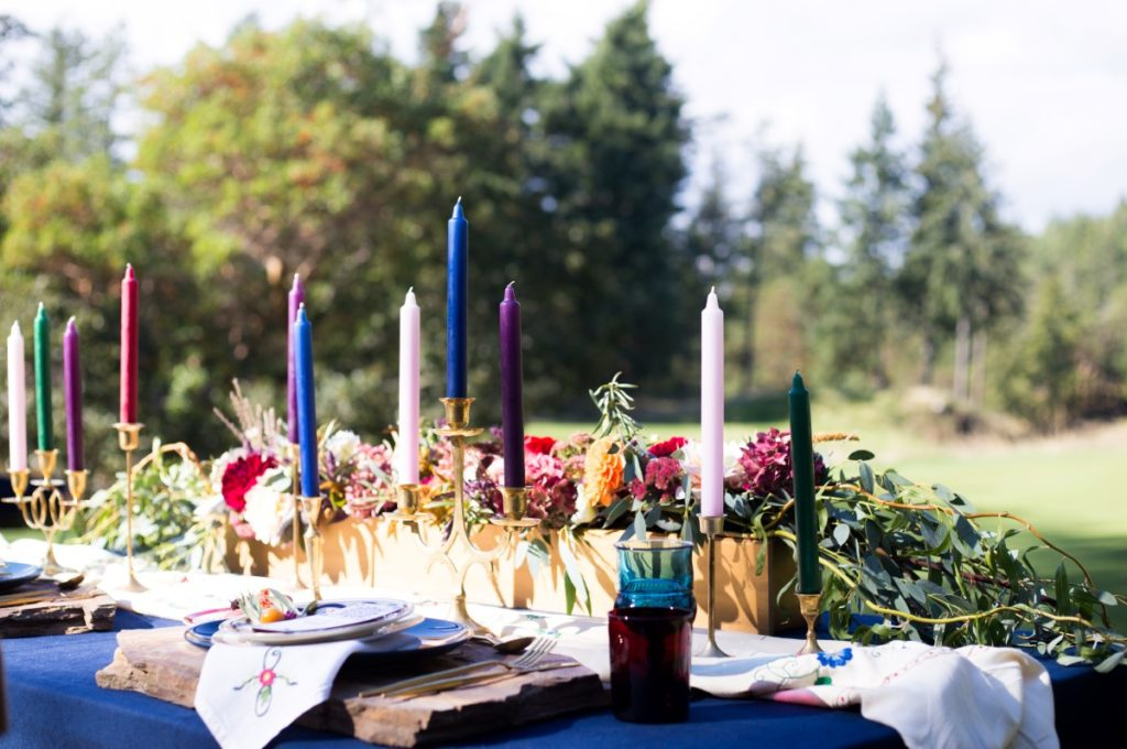 Spanish Style Coloured Candles on Outdoor Reception Table Vancouver Island Wedding Magazine