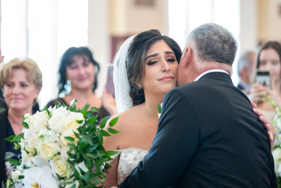 Bride and father hug at the front of Vancouver Church