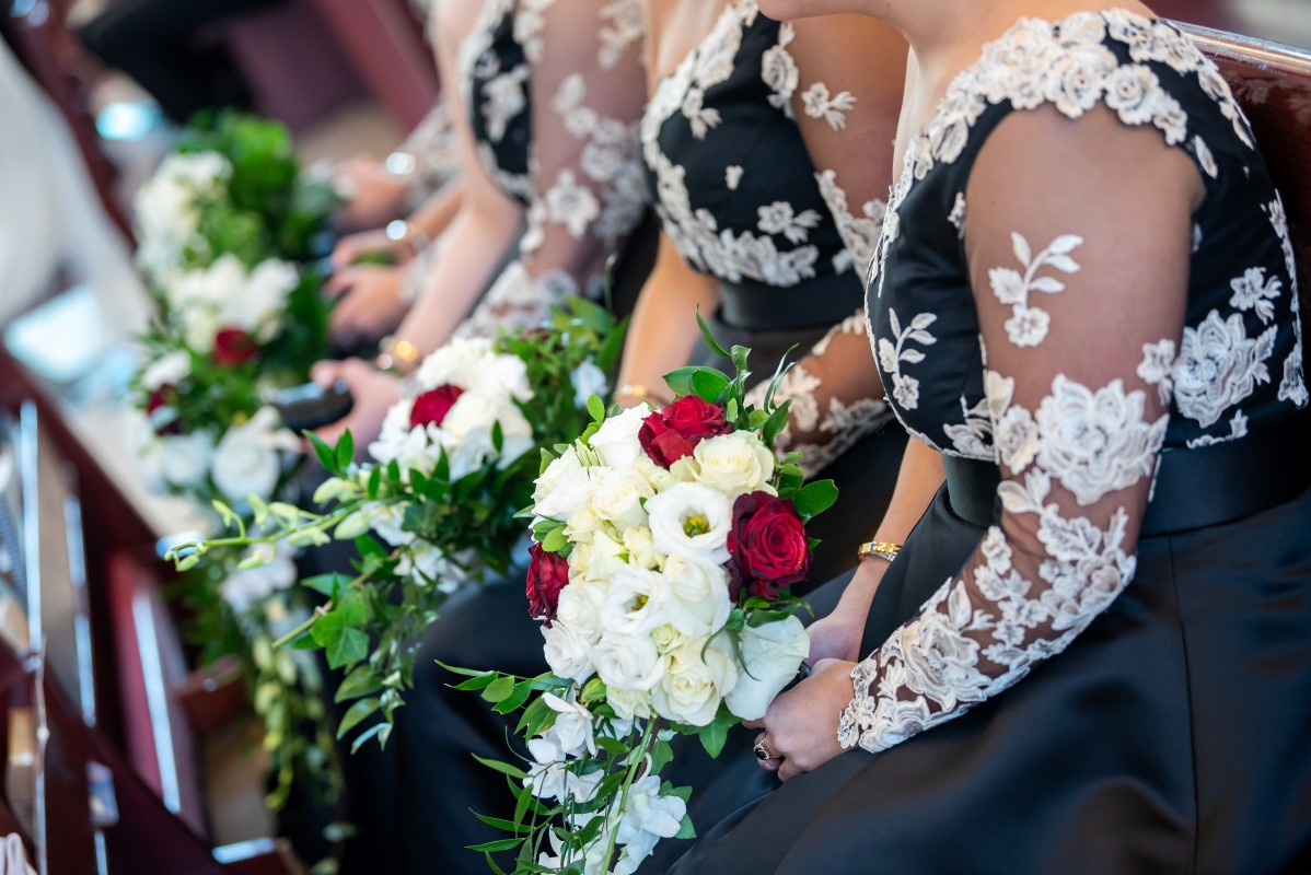Bridesmaids in black and white gowns carrying white dendrobium orchid bouquets