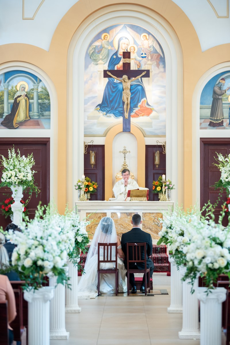 Bride and Groom sit at alter of church surrounded by white orchids