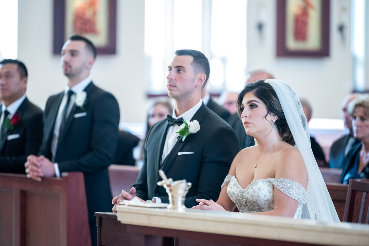 c89d4b7de2e ... Wedding couple kneel at the alter of Our Lady of Assumption Church in  Vancouver ...