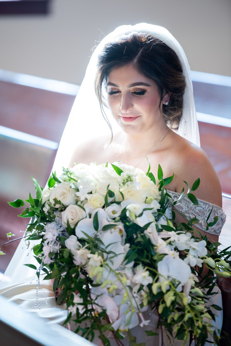 Light filters through bride's veil and white orchid bouquet