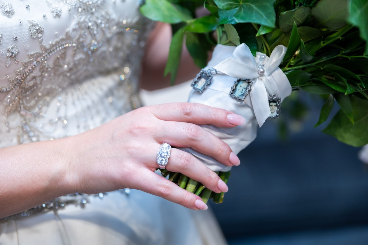 Bridal bouquet with charm photos of relatives not present at the wedding