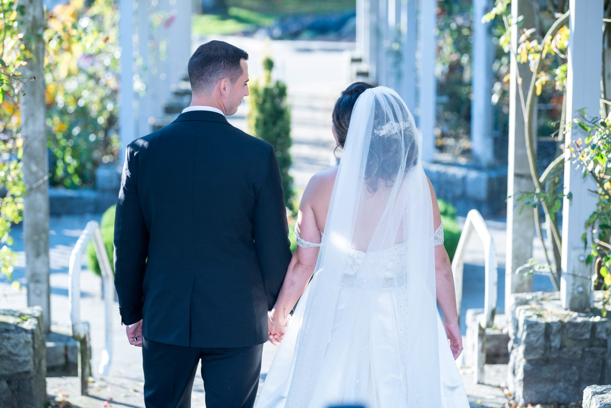 Bride and groom walk together holding handfs in a garden