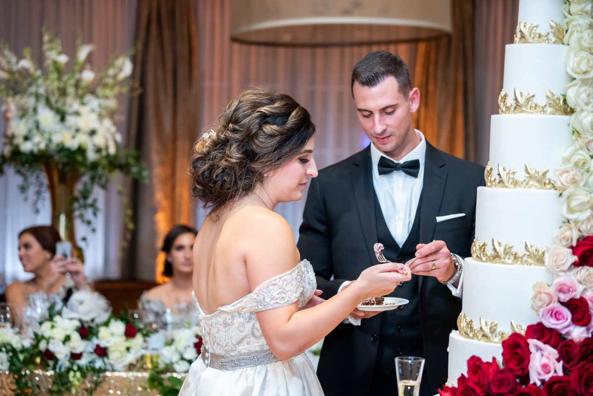 Newlyweds cut the five tier beige and gold wedding cake at Vancouver Club