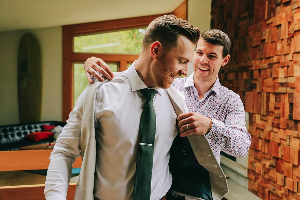 Tofino Elopement Groom puts on his jacket with best man before ceremony on Tonquin Beach