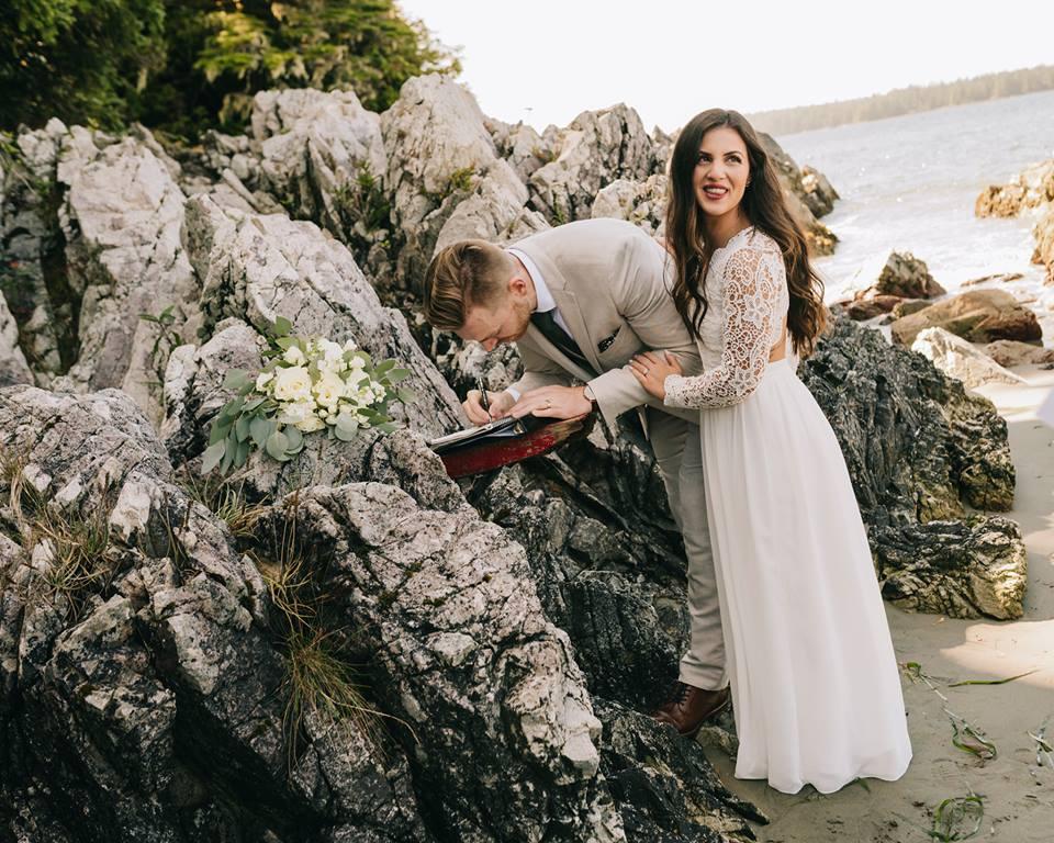 Tofino Elopment Couple signing the registrar on the rocks of Tonquin Beach Vancouver Island