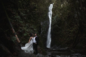 Bridal couple pose in front of waterfall on Vancouver Island