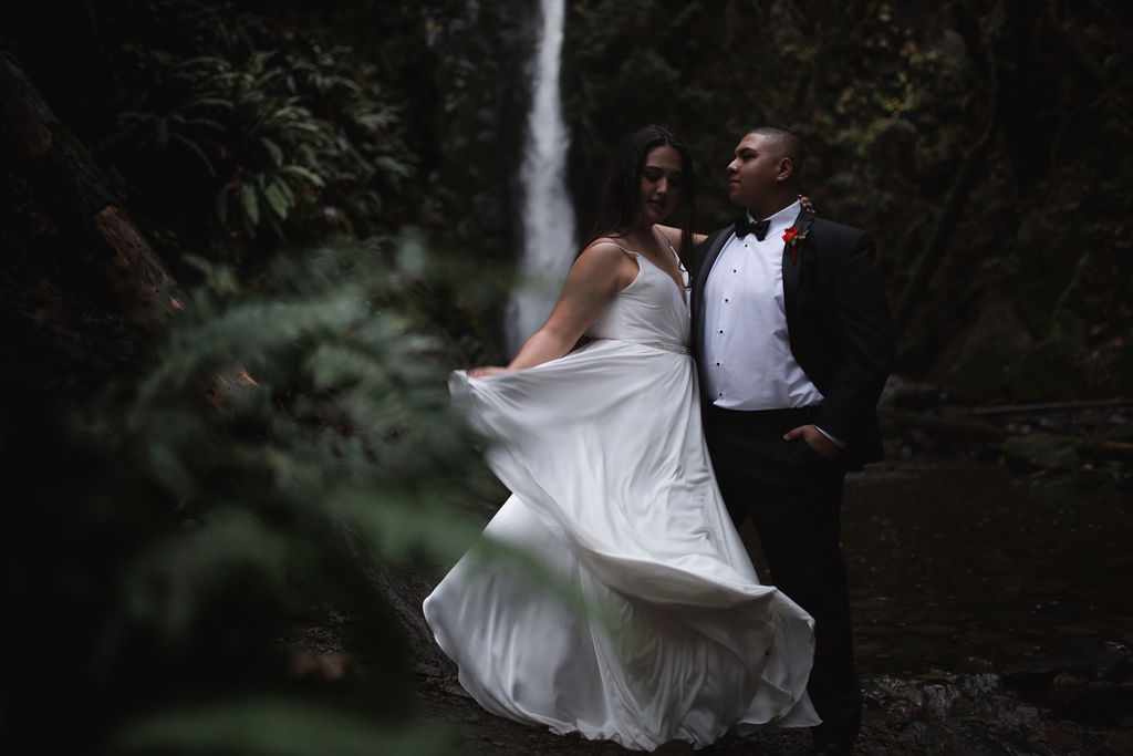 Bride twirls her dress and stands in front of waterfall with her groom