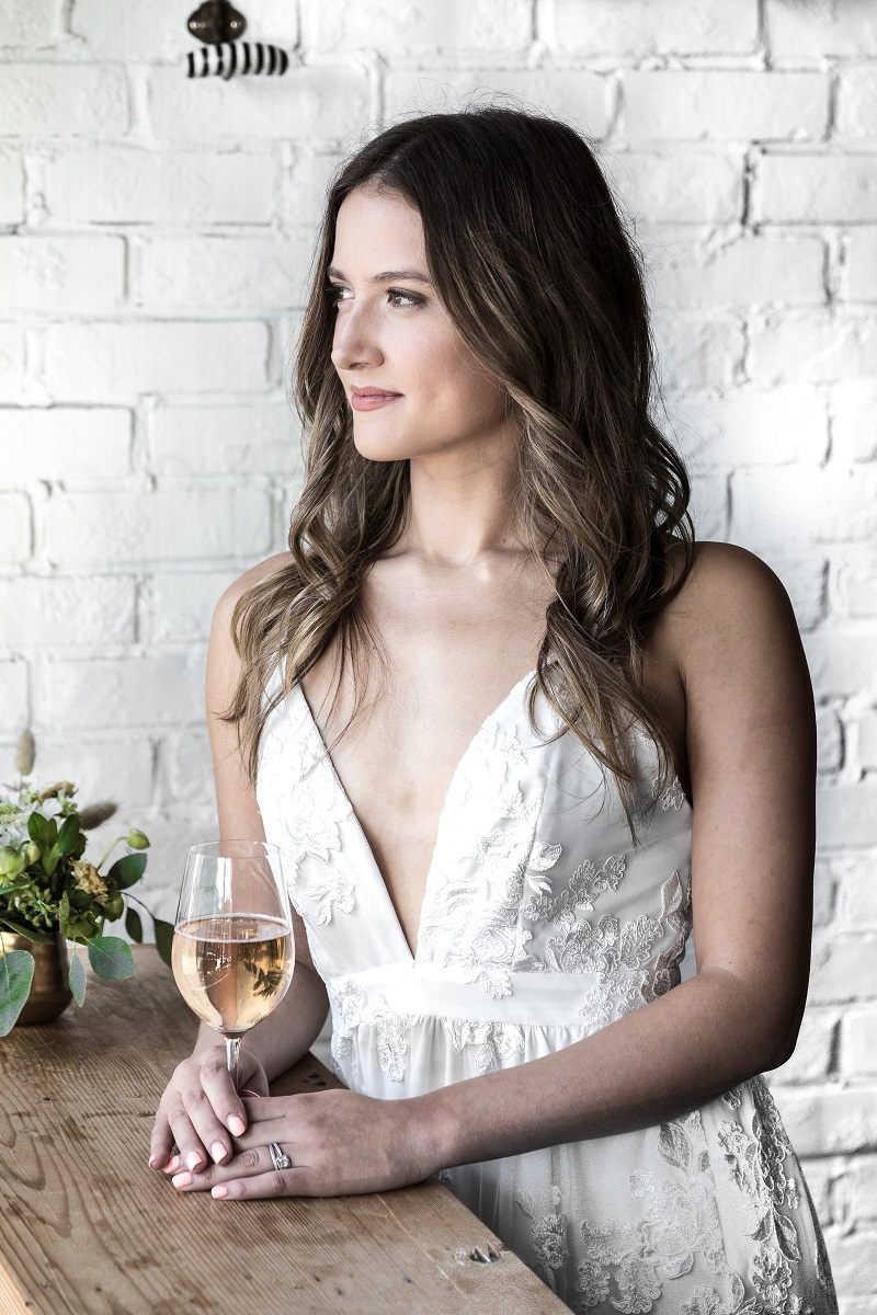 Chic City Bride in Park and Fifth Co weddin gown holding glass of wine at Burdock & Co in Vancouver