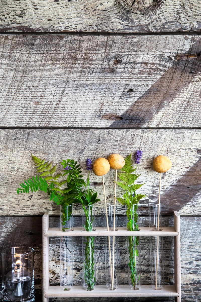 tulips and ferns in glass test tubes against distressed wall by Studio Full Bloom Vancouver Wedding