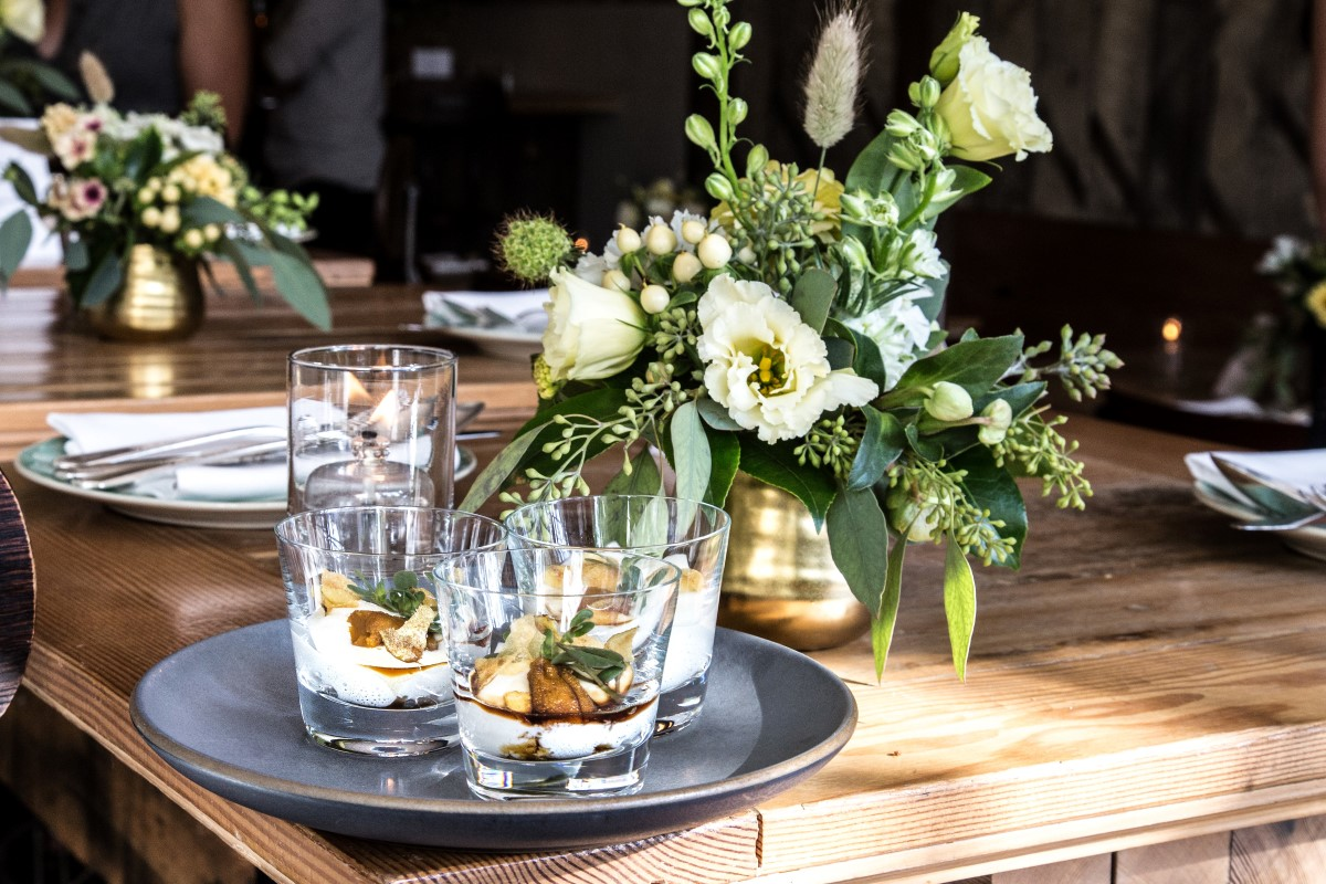Chic drinks and white floral arrangement on wedding reception table