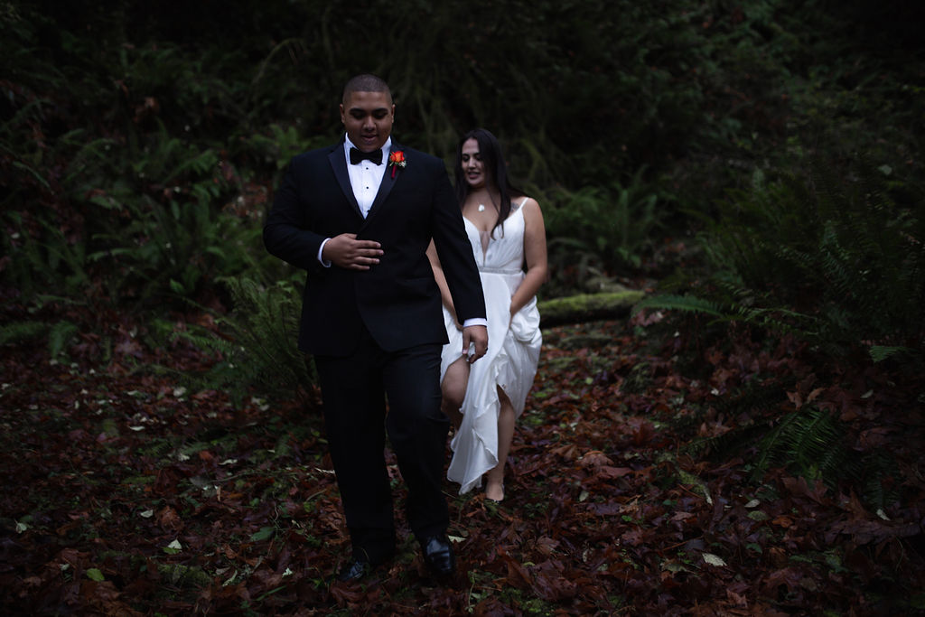 Waterfall Bride and Groom walk through the forest holding hands Vancouver Island
