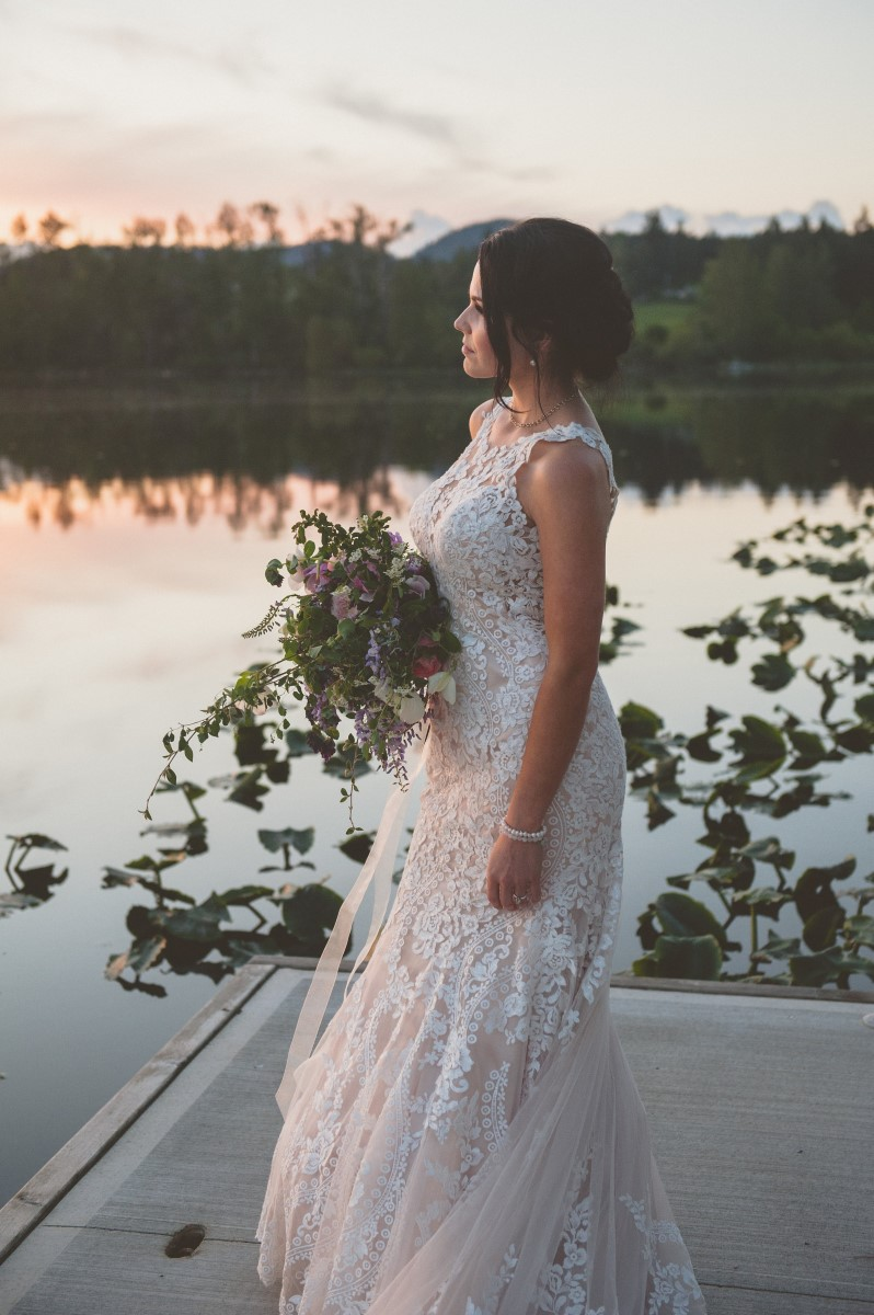 Bride on Lake Deck surrounded by water lilies and sunset Cowichan Bay Weddings
