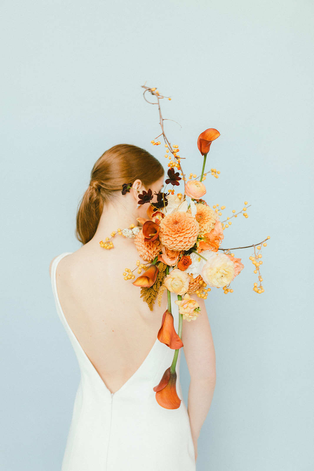 Open Back Bridal Gown with orange bridal bouquet in Vancouver Wedding Magazine