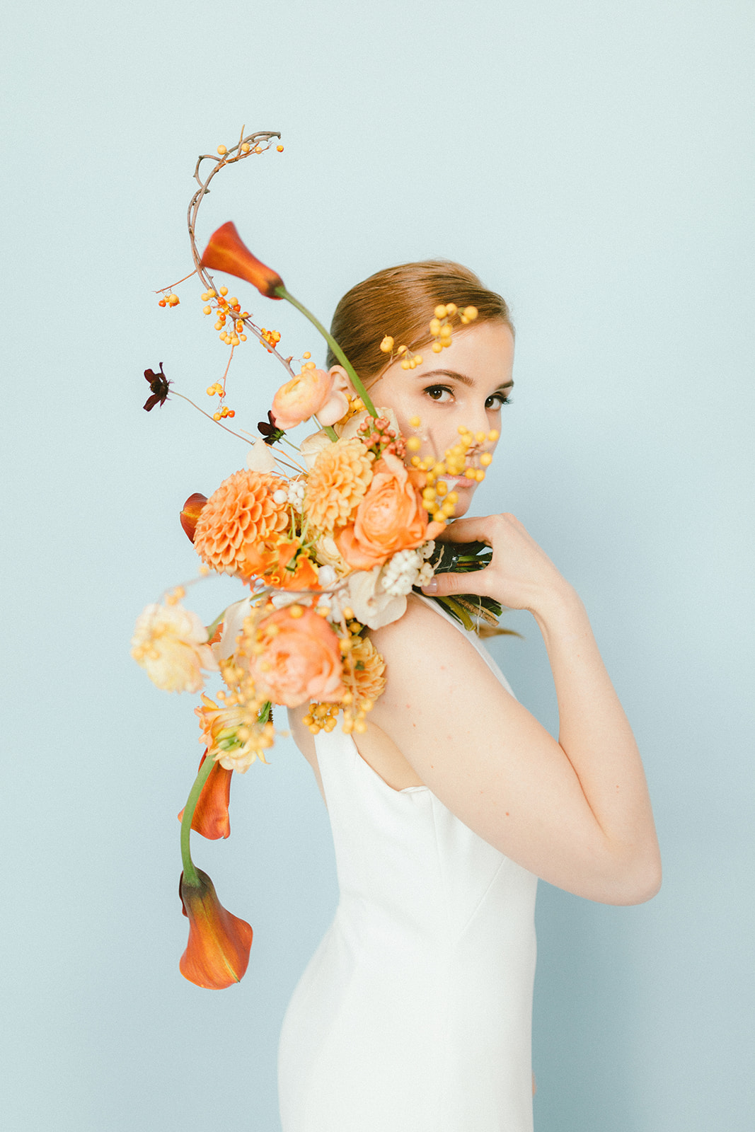 Vancouver Bride with red hair peeking behind her bouquet of orange dahlia and calla lily