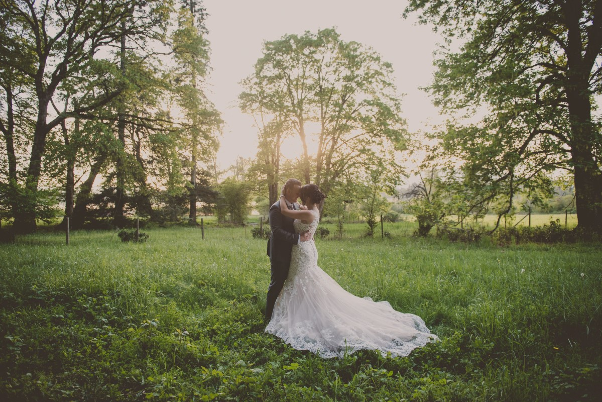Newlyweds in grass field with bridal train of lace Cowichan Valley