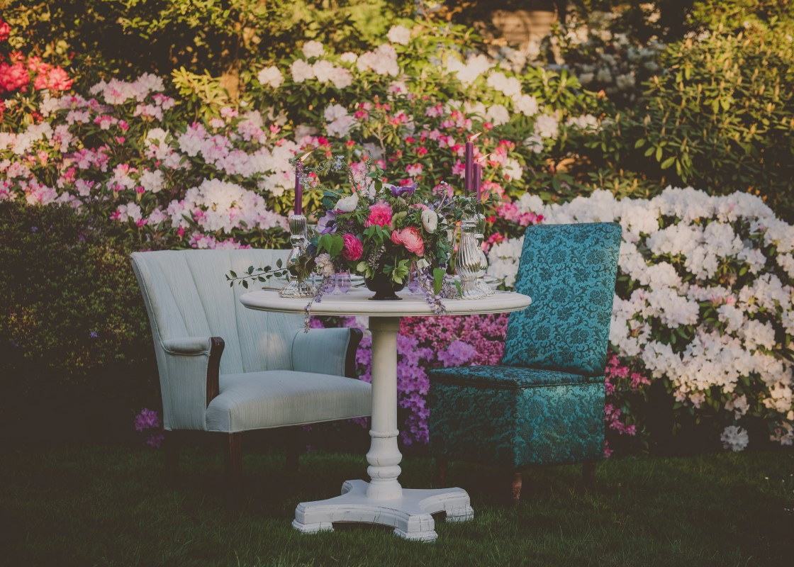 Table and two antique chairs in flower garden for wedding reception on Vancouver Island