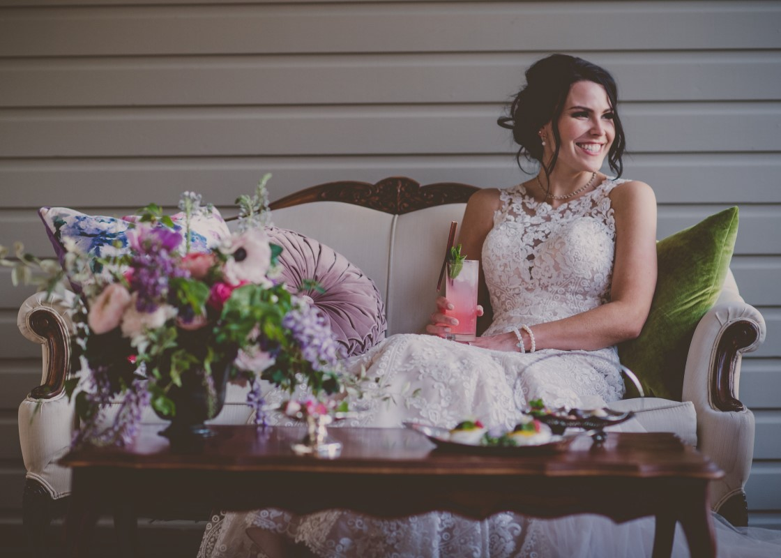 Bride enjoys drink on the deck filled with antique furniture and flowers