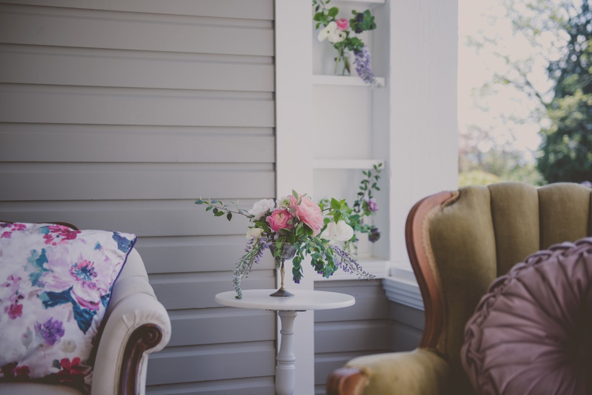 Florals sitting on side table with antique furniture West Coast Weddings