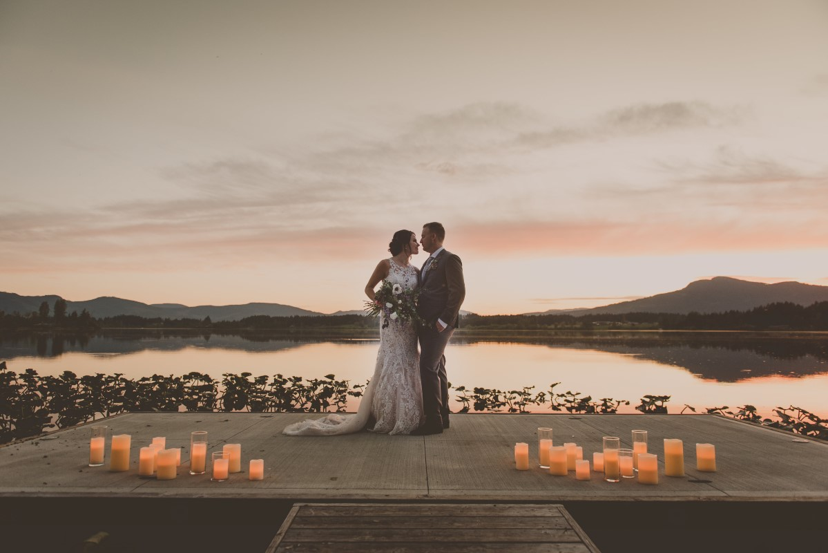 Couple in front of lake sunset surrounded by candles Vancouver Island Weddings