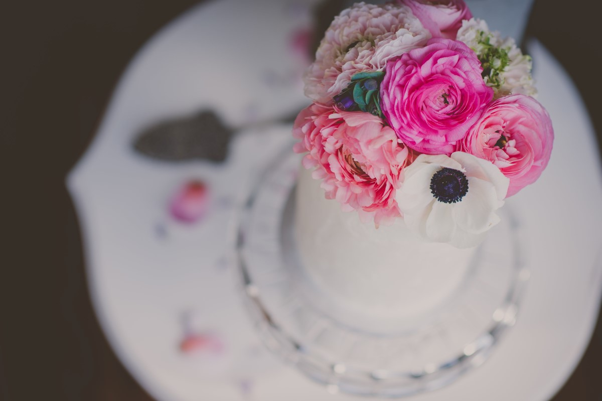 Pink flowers on white wedding cake and vintage plate Cobblehill Cake Co