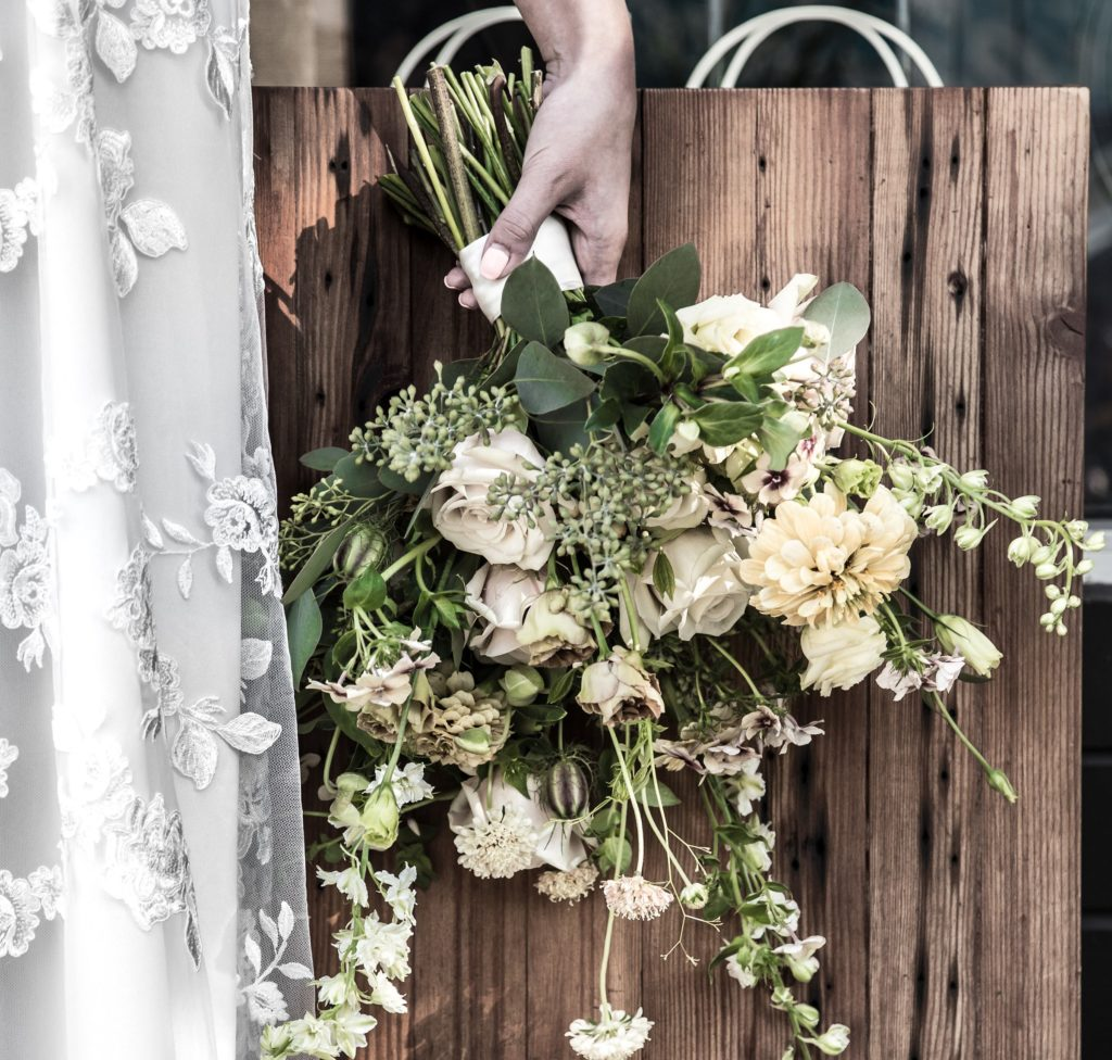 White bridal bouquet and lace overlay Park and Fifth Co wedding gown in Vancouver