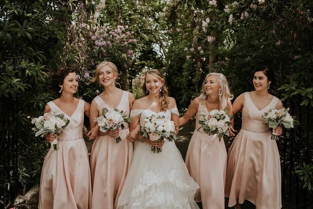Romantic Bridesmaids in blush pink gowns carrying bouquets of peonies and roses