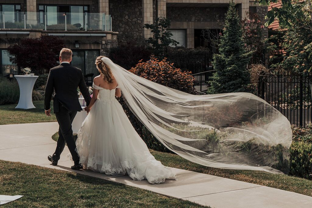 Newlyweds leave ceremony with bride's veil flying in the breeze