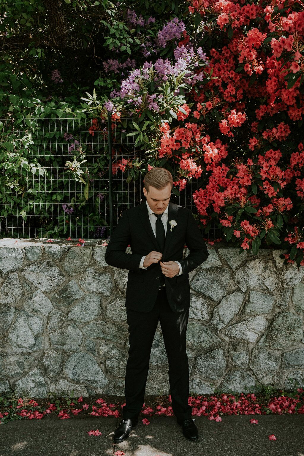 Groom buttons jacket of Indochino suit with pink flowers behind him
