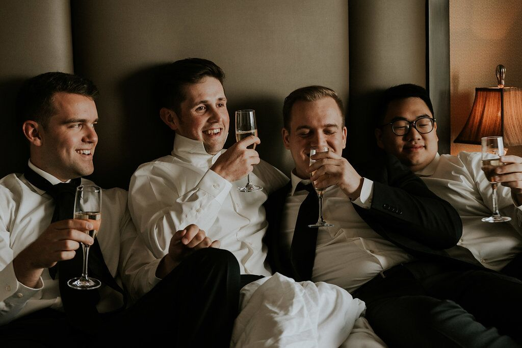 Groom and groomsman raise a glass all crowded onto bed at Oak Bay Beach HOtel