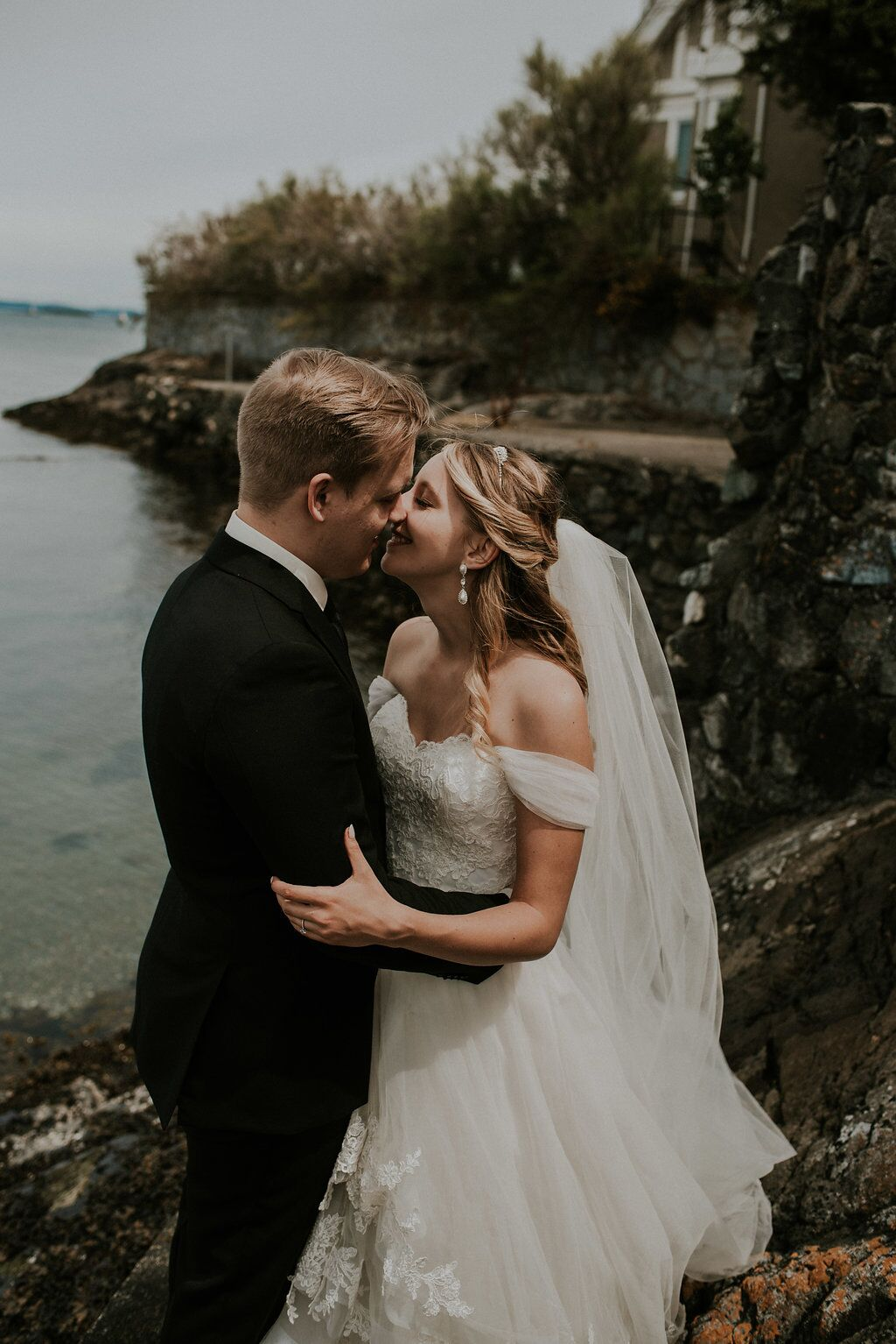 Romantic Newlyweds kiss above the ocean water on Vancouver Island