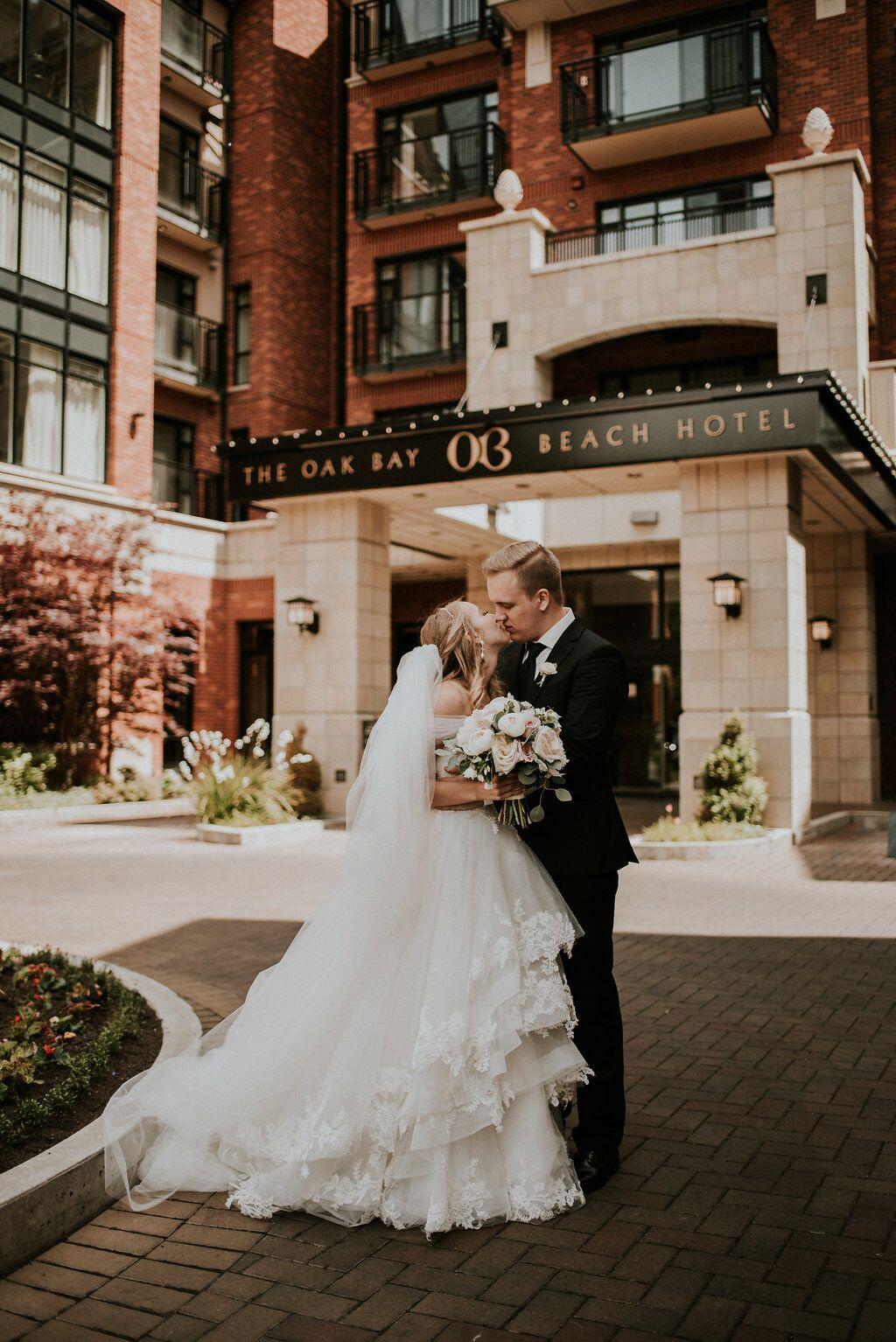 Romantic Newlyweds kiss at front door of Oak Bay Beach Hotel