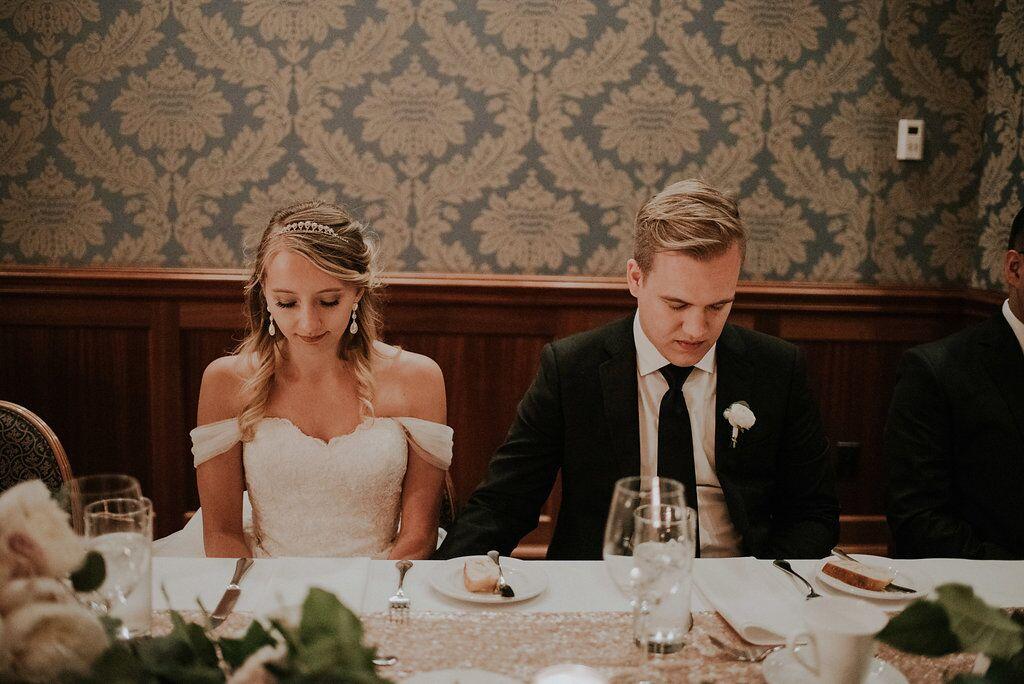 Romantic Newlyweds bow their head in prayer at Oak Bay Beach HOtel reception meal