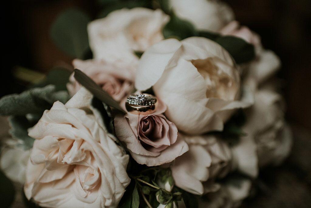 Romantic wedding rings on blush roses West Coast Weddings Magazine