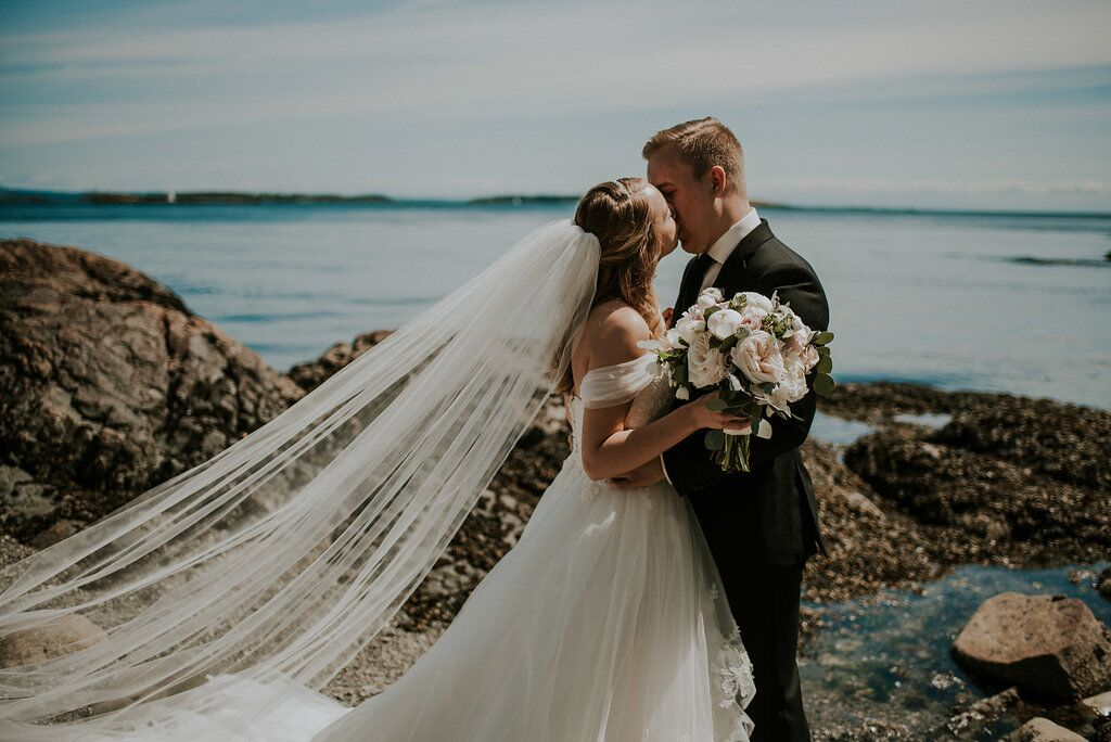 Romantic first look couple on the Vancouver Island ocean with bride in cathedral veil