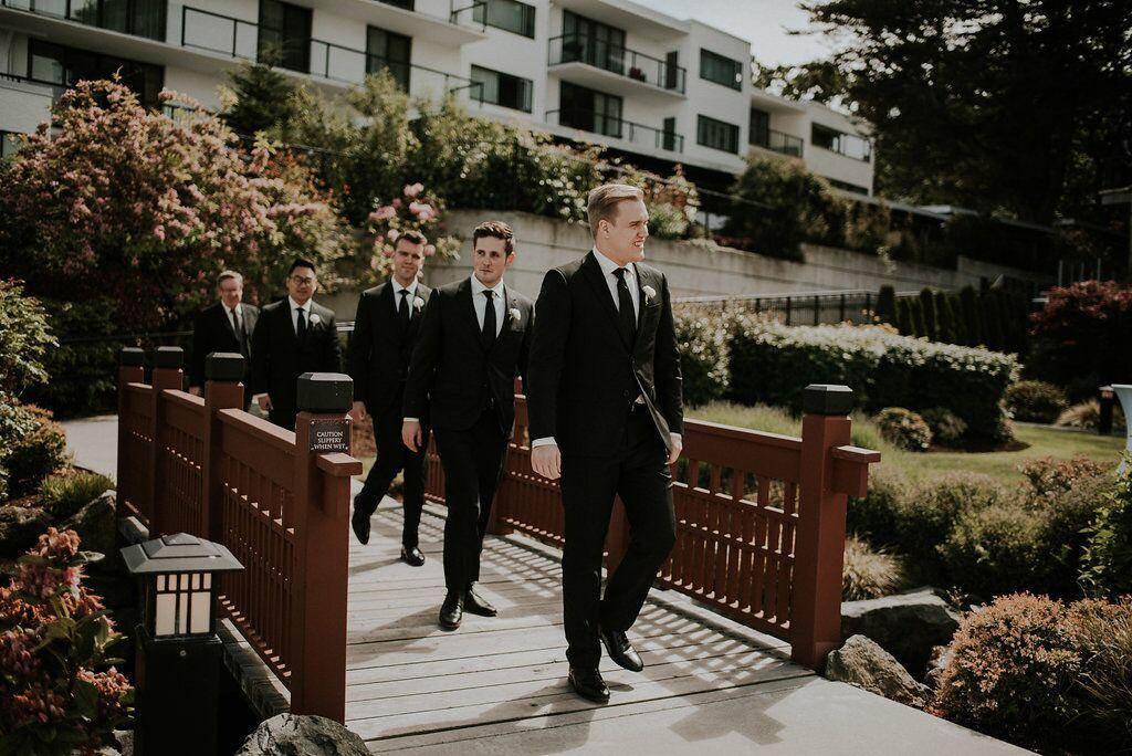 Groom and groomsman walk towards ceremony through garden bridge West Coast Weddings Magazine
