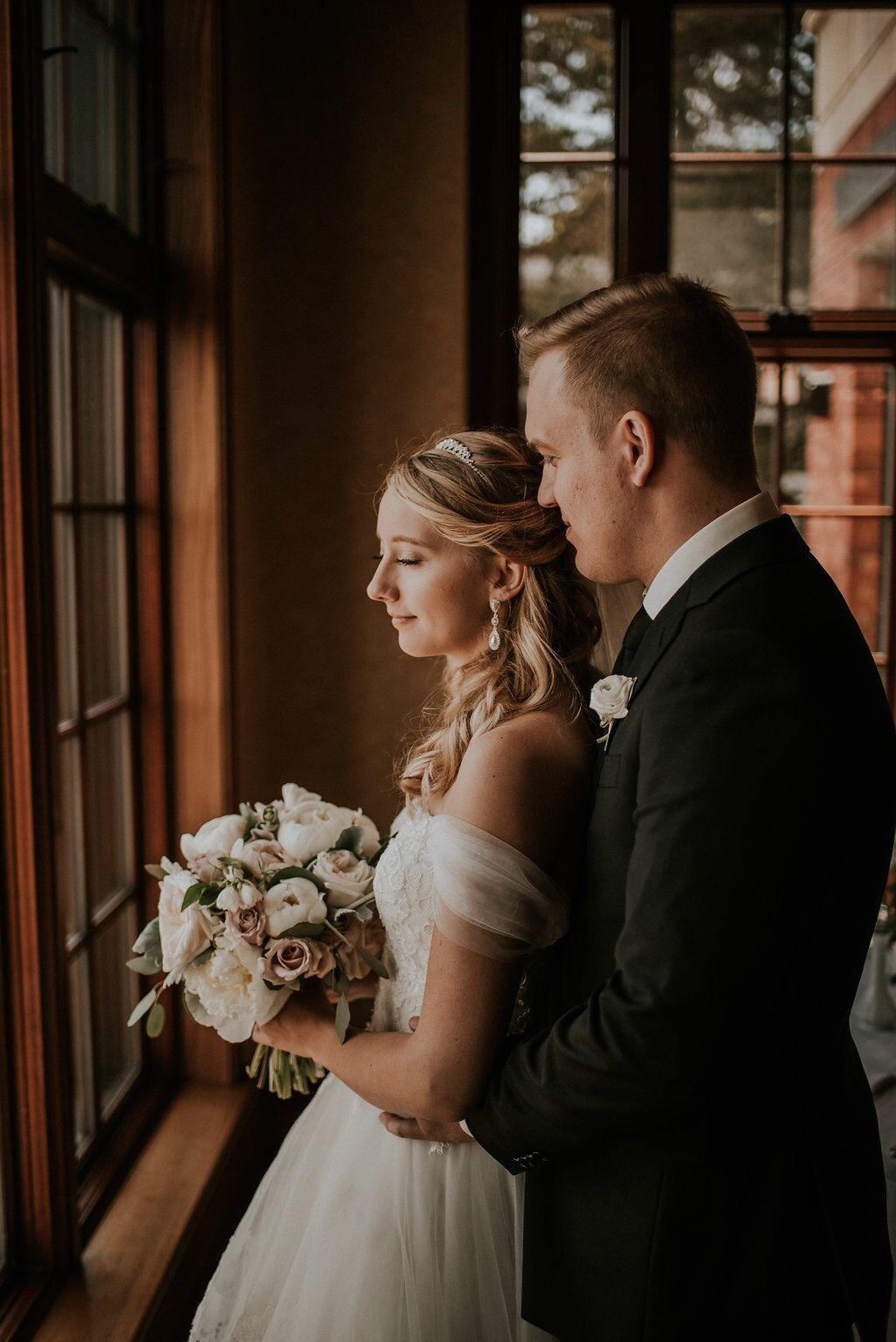 Romantic Newlyweds look out window of Oak Bay Beach Hotel
