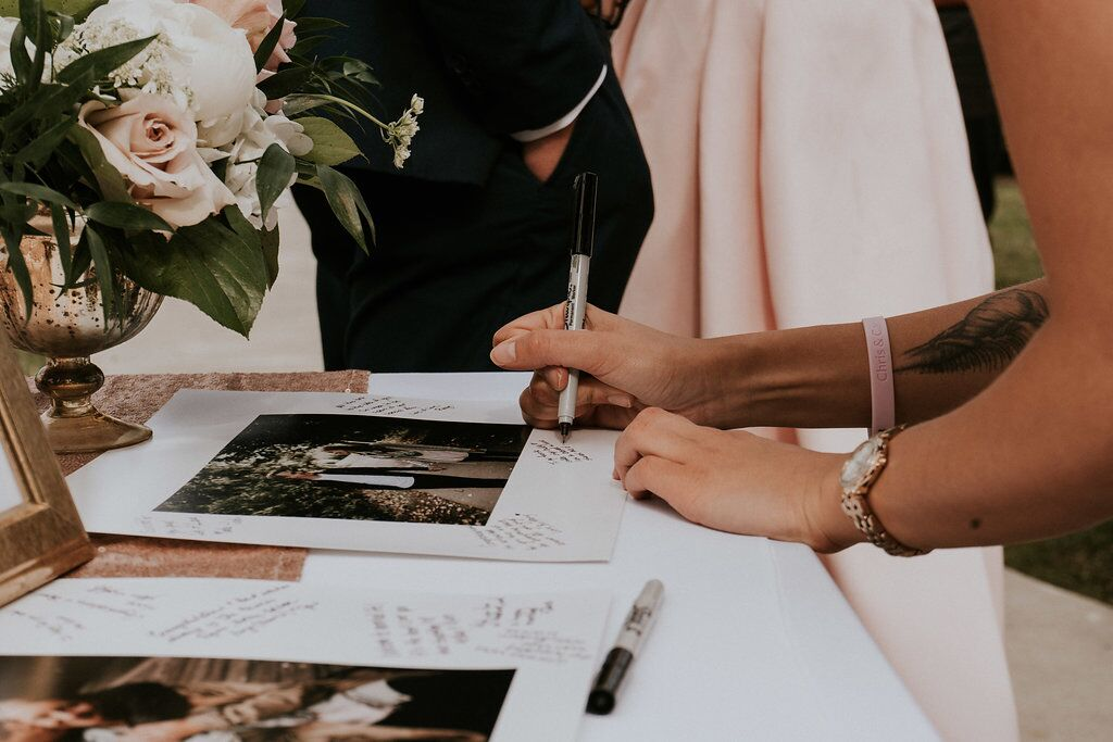 Guests signing photos of the newlyweds at wedding reception on Vancouver Island