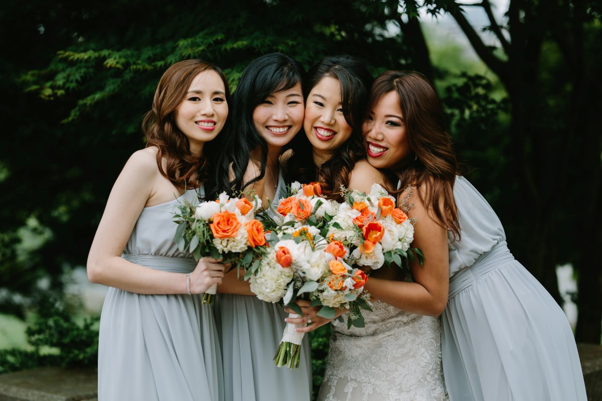 Chinese Fusion Wedding bride and bridesmaids in pastel dresses with orange and white bouquets
