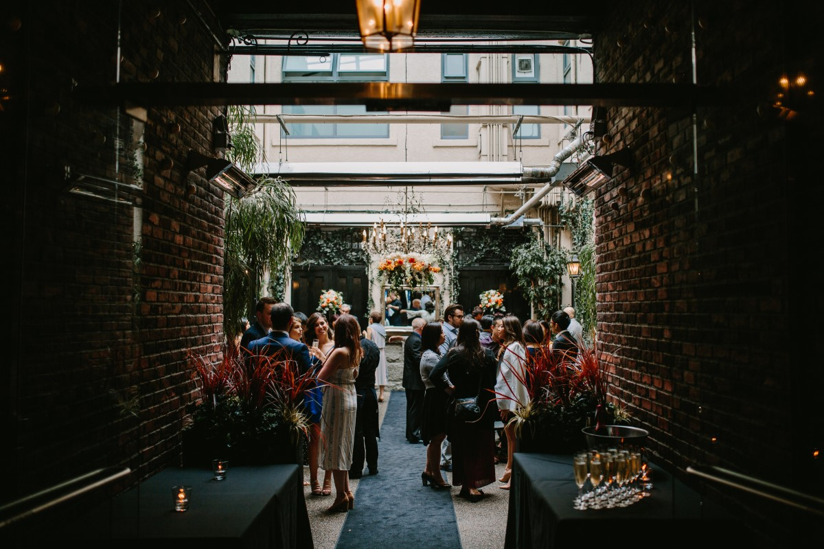 Chinese Fusion Wedding Couple exchange wedding vows in front of ivy backdrop in Vancouver